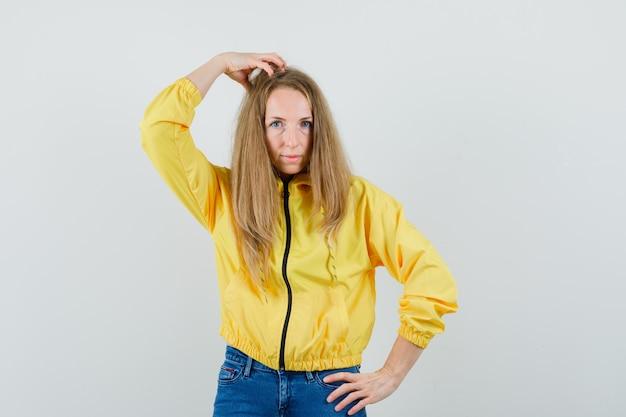 Signora bionda grattandosi la testa in giacca, jeans e guardando esitante,