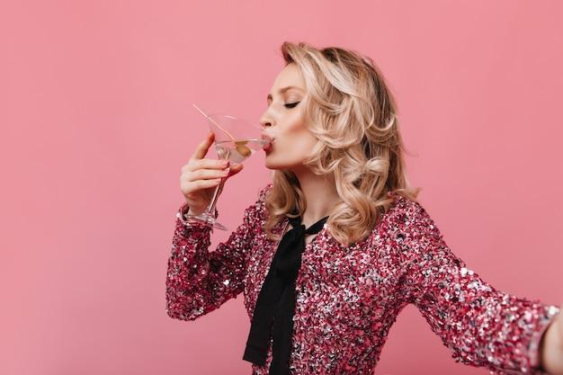 Signora bionda in camicetta con paillettes beve martini e prendendo selfie
