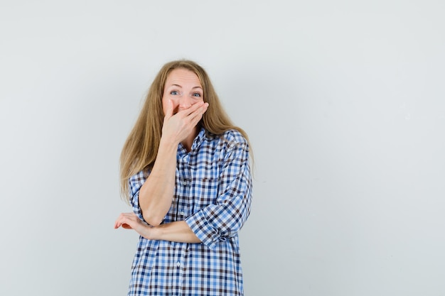 Signora bionda in camicia tenendo la mano sulla bocca mentre ride,