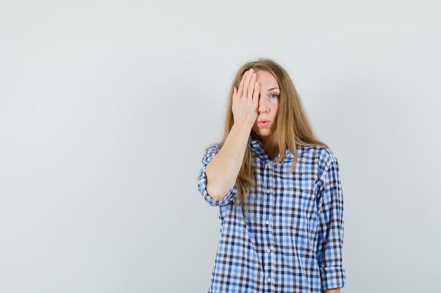 Signora bionda in camicia tenendo la mano su un occhio e guardando stupito,