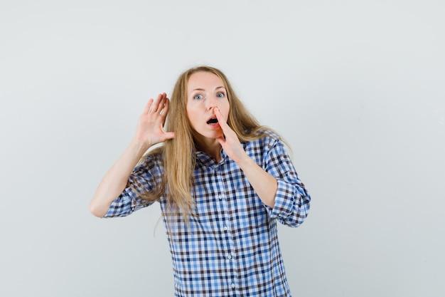 Signora bionda in camicia tenendosi per mano vicino alla bocca e all'orecchio e guardando curioso,