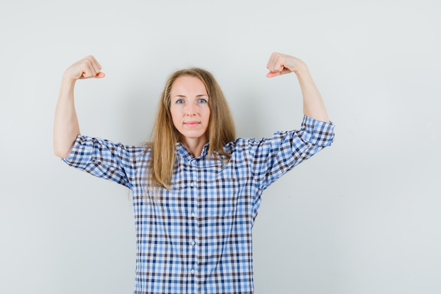 Blonde lady in shirt showing muscles of arms and looking strong ,