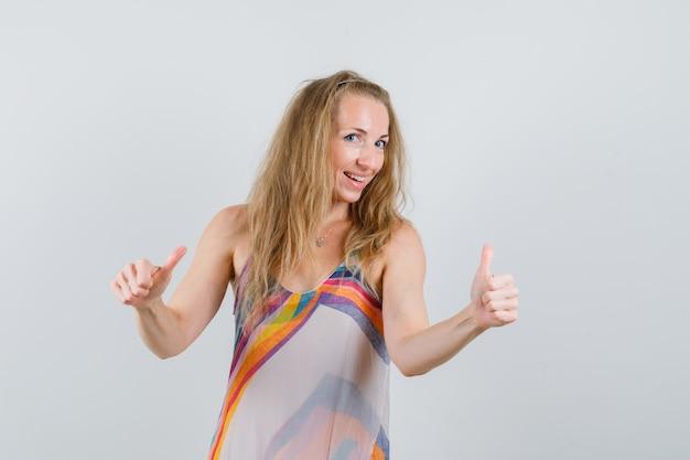 Блондинка в летнем платье показывает двойные пальцы вверх и выглядит весело
