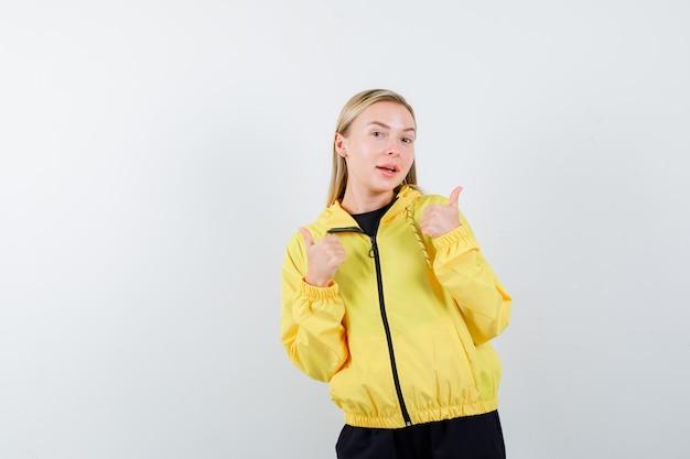 Блондинка в спортивном костюме показывает двойные пальцы вверх и выглядит весело. передний план.