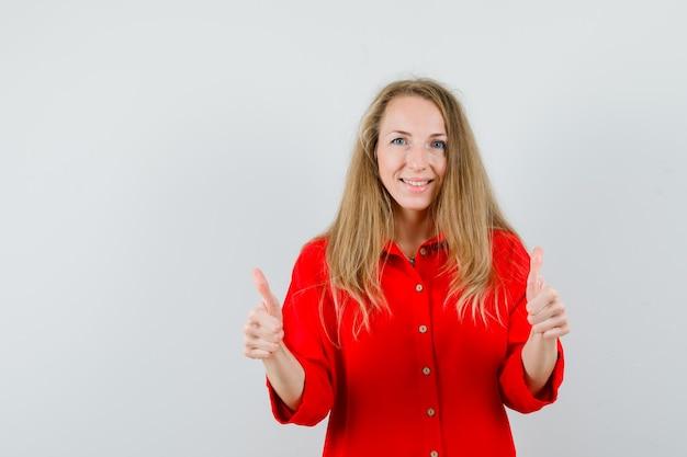 Signora bionda che mostra i doppi pollici in su in camicia rossa e sembra allegra,
