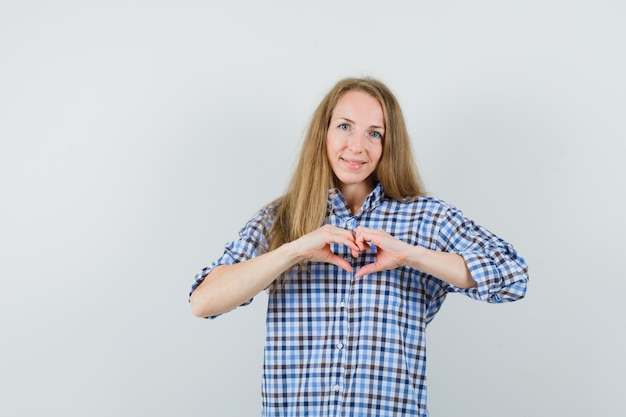 Blonde lady showing heart gesture in shirt and looking jolly.