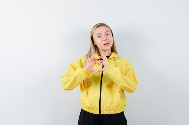Blonde lady showing heart gesture in tracksuit and looking cheery , front view.