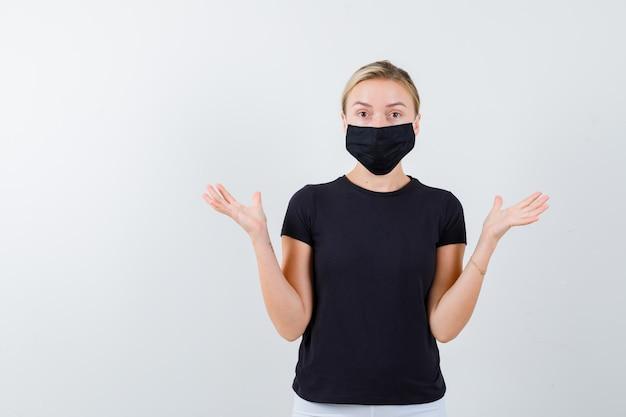 고립 된 검은 티셔츠에 무기력 한 제스처를 보여주는 금발 아가씨