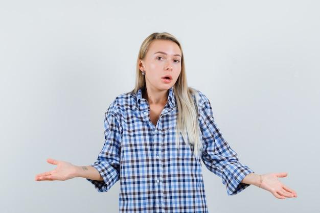 チェックシャツで無力なジェスチャーを示し、混乱しているように見えるブロンドの女性