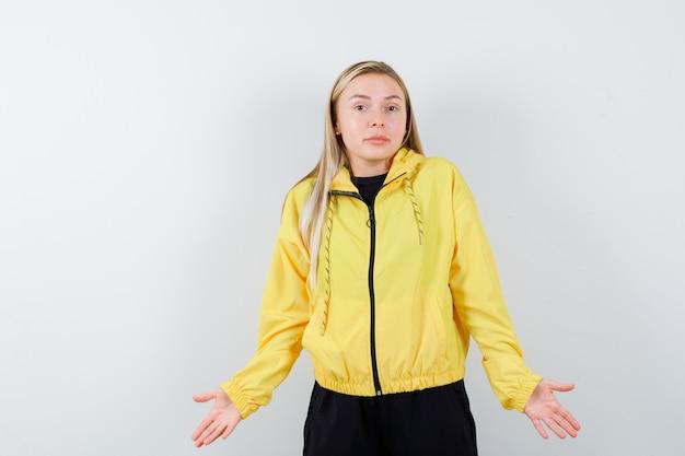 Signora bionda che mostra gesto impotente in tuta da ginnastica e che sembra confusa. vista frontale.