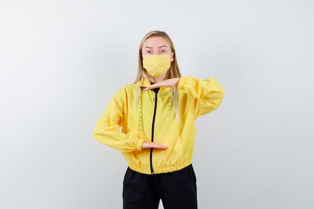 Tracksuit, 마스크에 큰 크기 기호를 표시 하 고 의아해, 전면보기를 찾고 금발 아가씨.