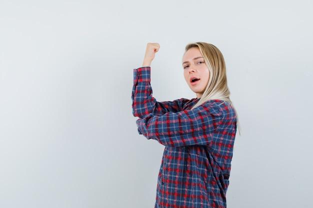 カジュアルなシャツで腕の筋肉を示し、自信を持って見える金髪の女性。正面図。