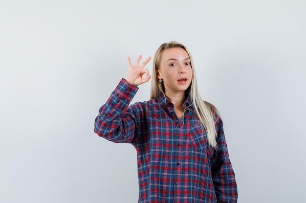 Signora bionda che mostra gesto giusto in camicia casual e sembra allegra. vista frontale.