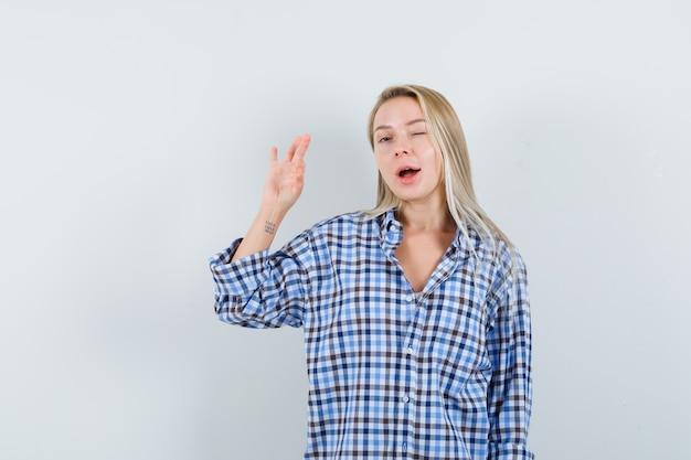 大丈夫なジェスチャーを示し、チェックのシャツで目をまばたきし、自信を持って見えるブロンドの女性