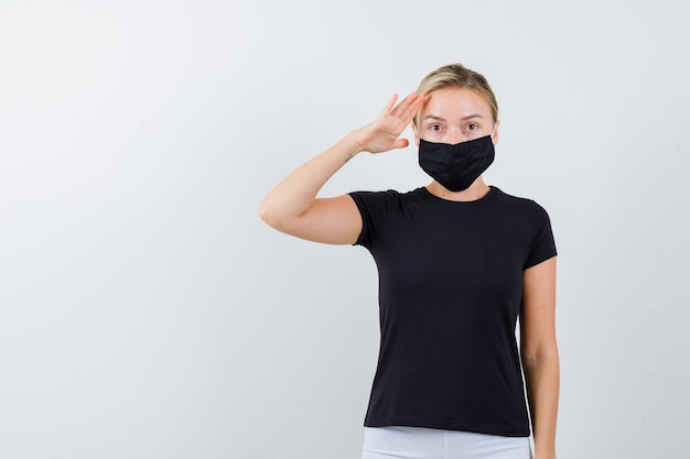 Blonde lady showing salute gesture in black t-shirt isolated