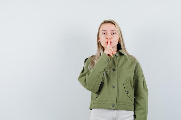 Блондинка показывает жест молчания в куртке, штанах и смотрит внимательно, вид спереди.