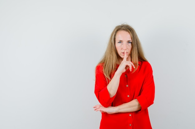 Blonde lady showing silence gesture in red shirt and looking careful ,
