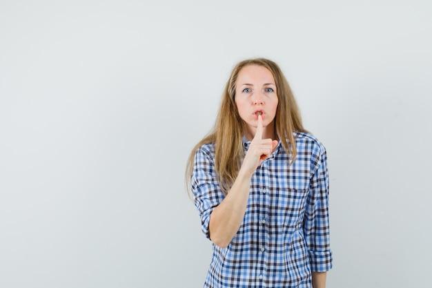 Signora bionda che mostra gesto di silenzio in camicia e guardando attento,