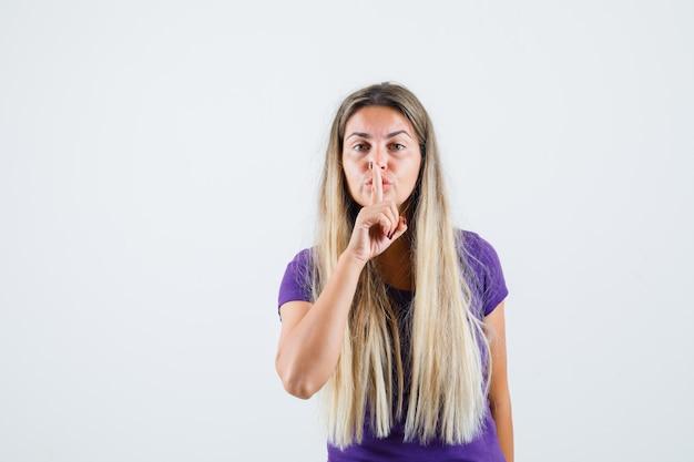 Signora bionda che mostra gesto di silenzio in maglietta viola e guardando attento, vista frontale.