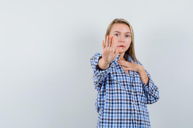 캐주얼 셔츠에 중지 제스처를 보여주는 금발 아가씨와 불안을 찾고