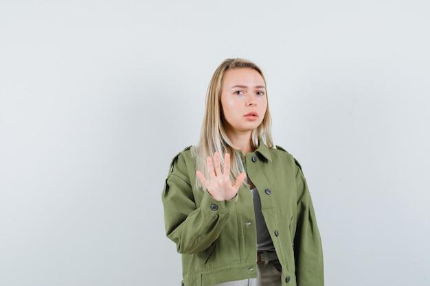 재킷에 중지 제스처를 보여주는 금발 아가씨는 무서워, 전면보기.
