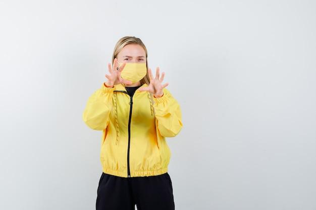 운동복, 마스크 및 혐오, 전면보기에서 중지 제스처를 보여주는 금발 아가씨.