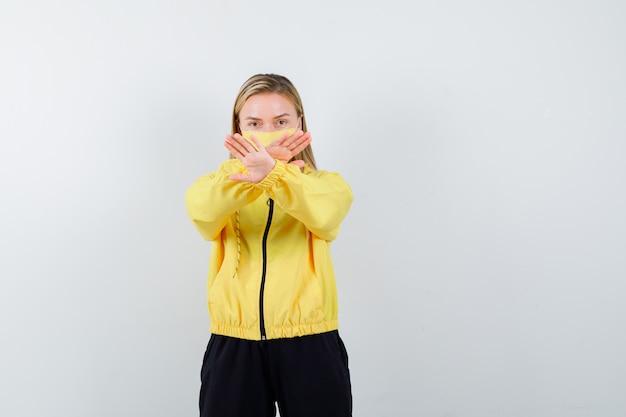 Signora bionda che mostra il gesto di arresto in tuta da ginnastica e guardando fiducioso, vista frontale.