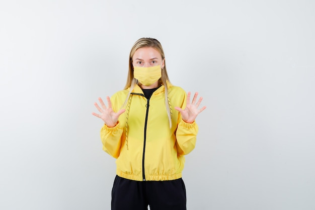 Signora bionda che mostra il gesto di arresto in tuta da ginnastica e sembra spaventata, vista frontale.