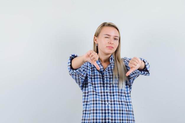 親指を下に見せて、チェックのシャツで目をまばたきし、自信を持って見えるブロンドの女性