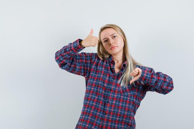カジュアルなシャツで親指を上下に示し、躊躇している金髪の女性、正面図。