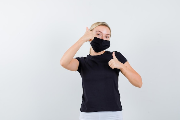 黒のtシャツ、黒のマスクで親指を表示し、満足している金髪の女性