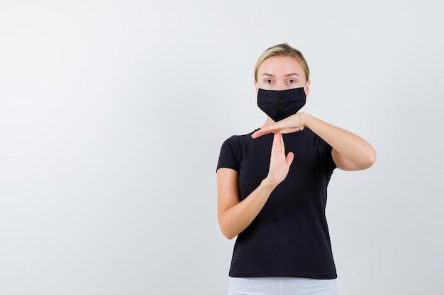 Блондинка показывает жест перерыва в черной футболке, черной маске и выглядит уверенно