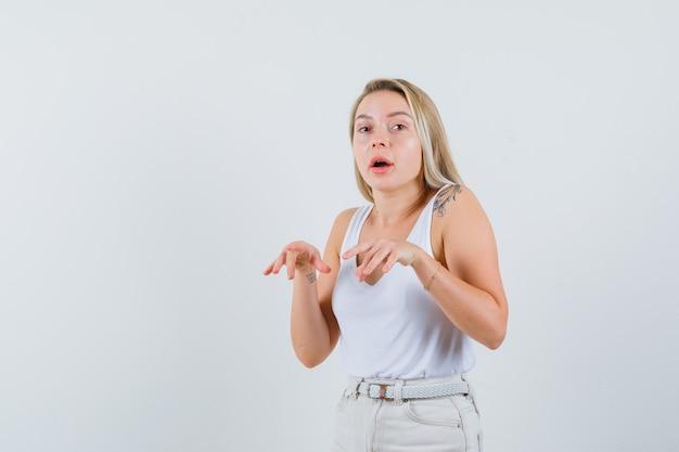 중항, 바지, 전면보기에 쥔 손가락으로 입력 제스처를 보여주는 금발 아가씨.