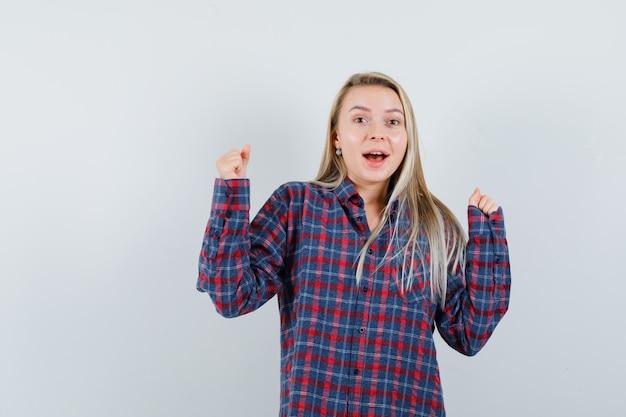 캐주얼 셔츠에 우승자 제스처를 보여주는 금발 아가씨와 행복, 전면보기를 찾고.