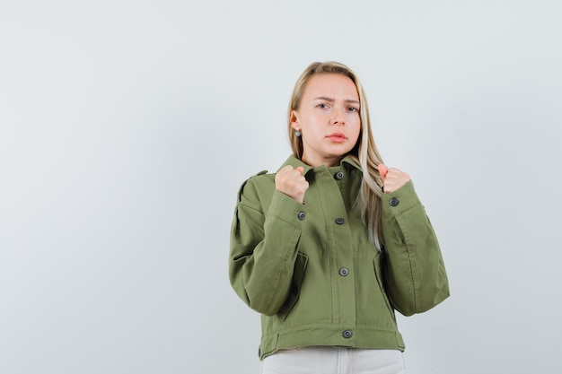 권투 선수에 서있는 금발 아가씨는 재킷, 바지에 포즈를 취하고 짓궂은, 전면보기를 찾고 있습니다.