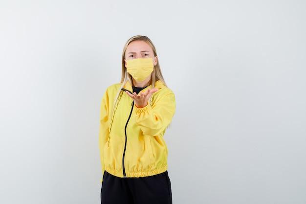 Блондинка протягивает руку в вопросительном жесте в спортивном костюме, маске и выглядит сердитой, вид спереди.