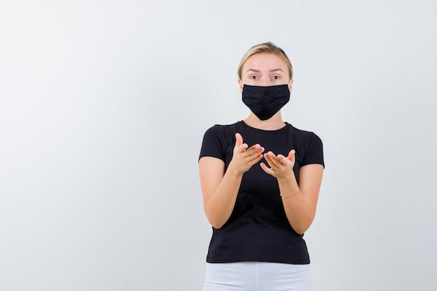 Signora bionda che allunga le mani davanti in maglietta nera, maschera nera e sembra perplessa