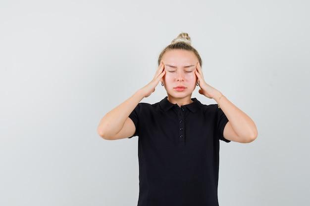 검은 티셔츠에 두통으로 고통 받고 피곤한 금발 아가씨. 전면보기.