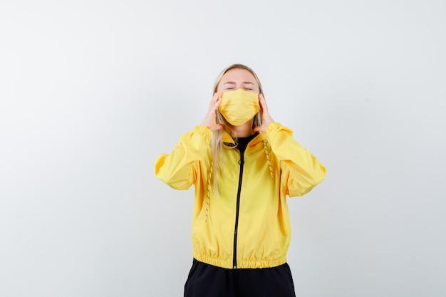 トラックスーツ、マスク、イライラして頭痛に苦しんでいる金髪の女性。正面図。
