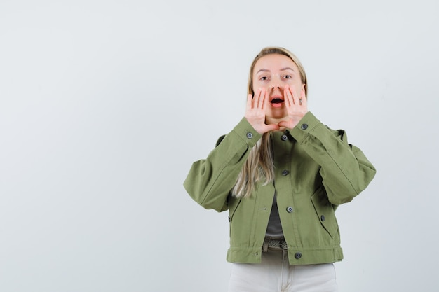 Блондинка рассказывает секрет или объявляет что-то в куртке, штанах и выглядит возбужденным. передний план.