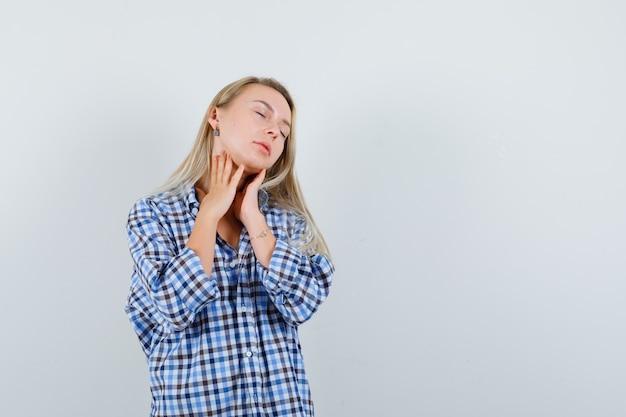 チェックシャツで首の肌に触れて繊細に見える金髪の女性