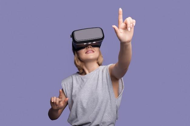 Блондинка трогает что-то в гарнитуре виртуальной реальности на фиолетовой стене