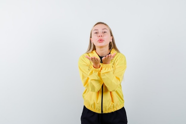 Blonde lady in tracksuit blowing air kiss with pouted lips and looking cute , front view.