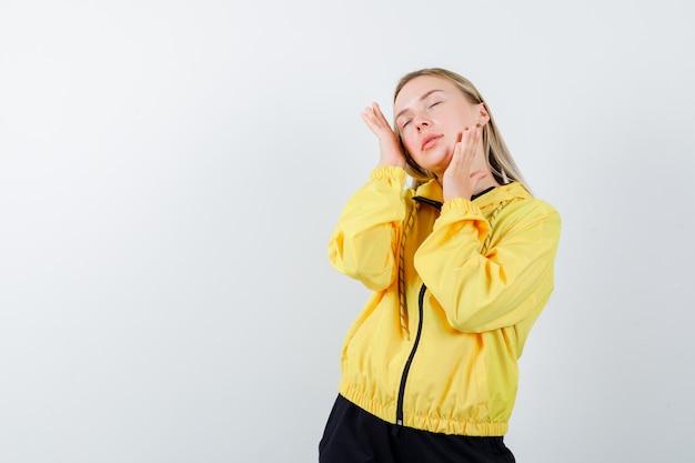 Signora bionda in tuta che esamina la pelle del viso toccando le guance e guardando rilassato, vista frontale.