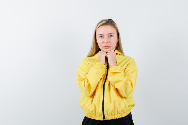 Signora bionda in tuta da ginnastica che si tiene per mano sotto il mento e che sembra sensibile, vista frontale.