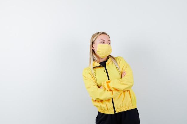 Signora bionda in tuta da ginnastica, maschera tenendo le braccia conserte e guardando pensieroso, vista frontale.