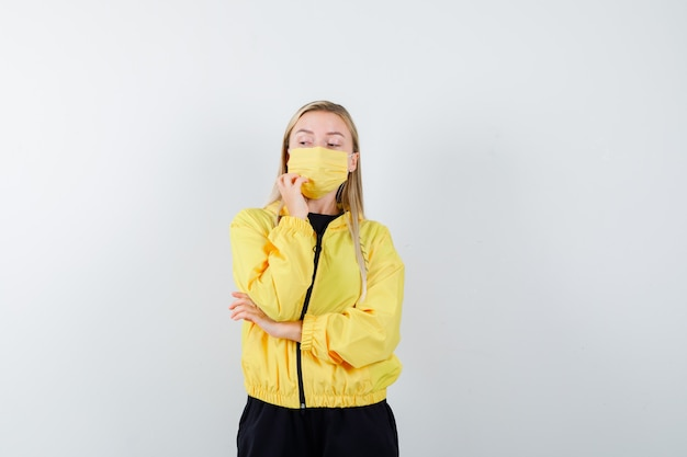 Signora bionda in tuta da ginnastica, maschera tenendo la mano sul mento e guardando pensieroso, vista frontale.