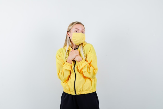 Signora bionda in tuta da ginnastica, maschera tenendo le mani sul petto e guardando gioiosa, vista frontale.