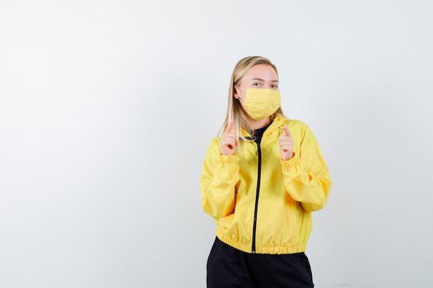 Signora bionda in tuta da ginnastica, maschera che punta alla telecamera e guardando fiducioso, vista frontale.
