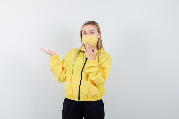 Signora bionda in tuta da ginnastica, maschera che finge di mostrare qualcosa, tenendo la mano sulla bocca e guardando sorpreso, vista frontale.